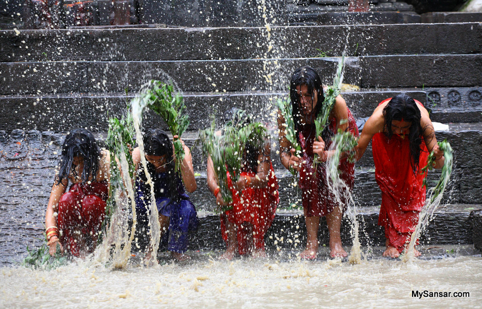 Young girls spread waters with helps of bushes while taking holy bath during Rishi Panchami festival.  Celebrated on the Panchami (Fifth Day) of Shukala Paksha (Waxing moon period) in the Hindu Month of Bhadrapada, Nepali women take a holy both early in the morning to mark the Rishi Panchami Festival and seek forgiveness from Sapta Rishis( seven saints) for the sins committed during their monthly periods throughout the year. Photo By: Shruti Shrestha