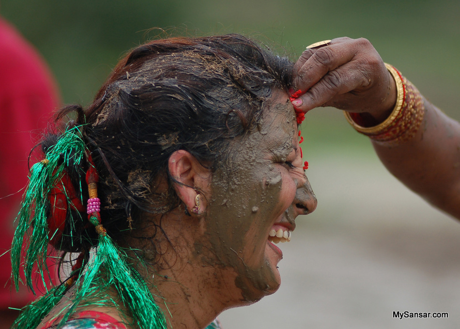 A woman in her smiley and mud her face during Aasar-15 festival, popularly known as Paddy Day (Dhan Diwash) Photo:  Bikash Dware