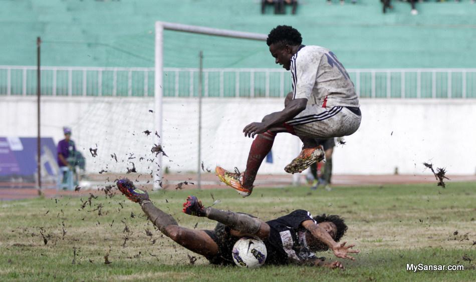 Sunday Eze Lawrence of Three Star Club (white jersey) jumps as Saroj Dahal of Madhyapur Youth Association tackles the balls during NCell Cup Football Tournament at Dashrath Stadium, Tripureshwor, Kathmandu on Thursday.  photo by kaushal adhikari