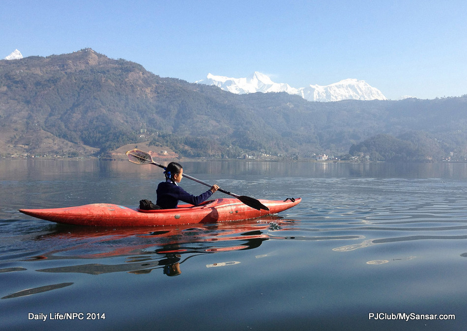 Rowing to and fro from school on a kayak is a daily routine for this young girl from Anadu near Phewa Taal. Photo: Purna Chandra Neupane