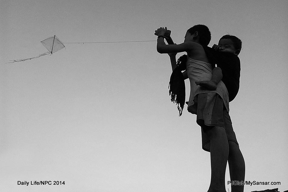 A boy carries his sib on his back as he flies a kite. Photo: Manjil Joshi