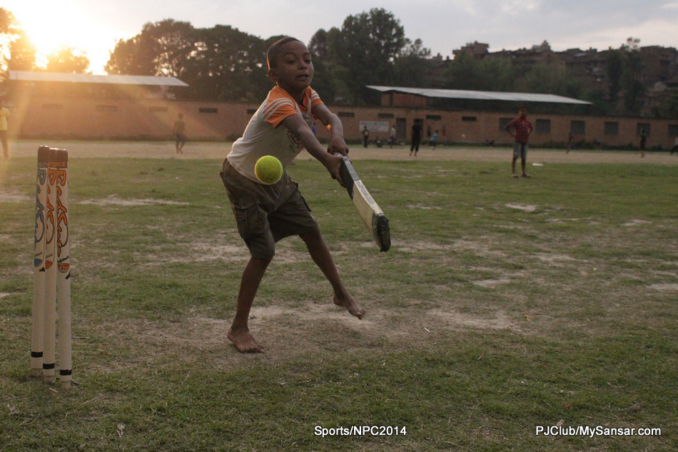 A kid attempts to defend the wickets as he strikes the ball. Photo: Nawa Bijay Shrestha