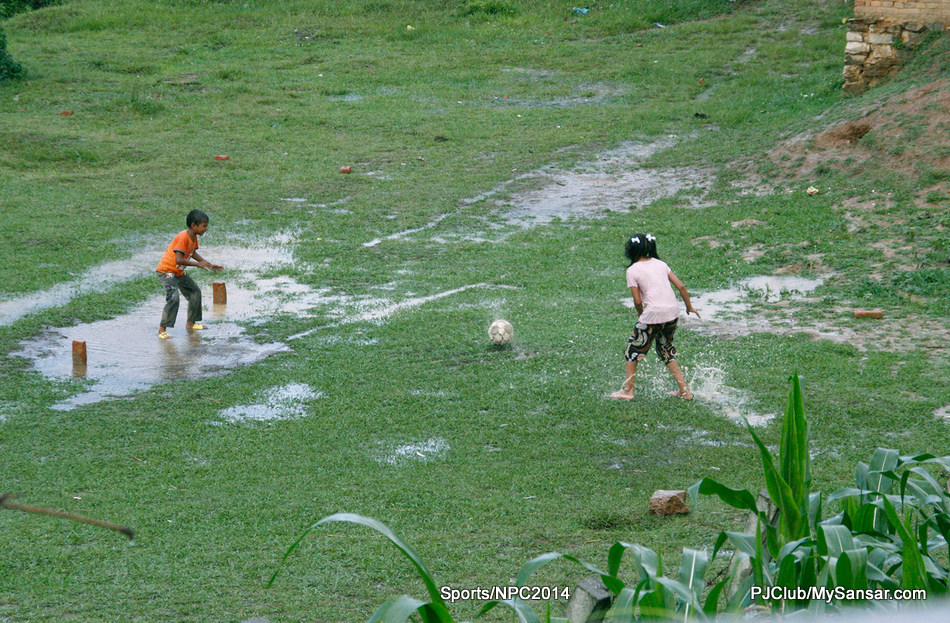 A young girl takes a penalty shot as a young boy readies to defend the makeshift post. Photo: Sajeen Maharjan.