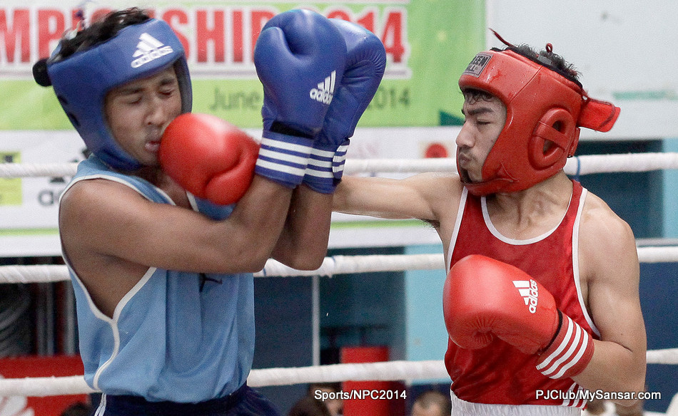 Two boxers exchange punches during the nationwide Novice boxing Championship held in Kathmandu. Championship bouts consists of 12 rounds and non-championship bouts consists of 10 rounds. An amateur bout however consists of four and the number of rounds gradually increases as the boxer turns pro. (Yatra Thulung Rai)