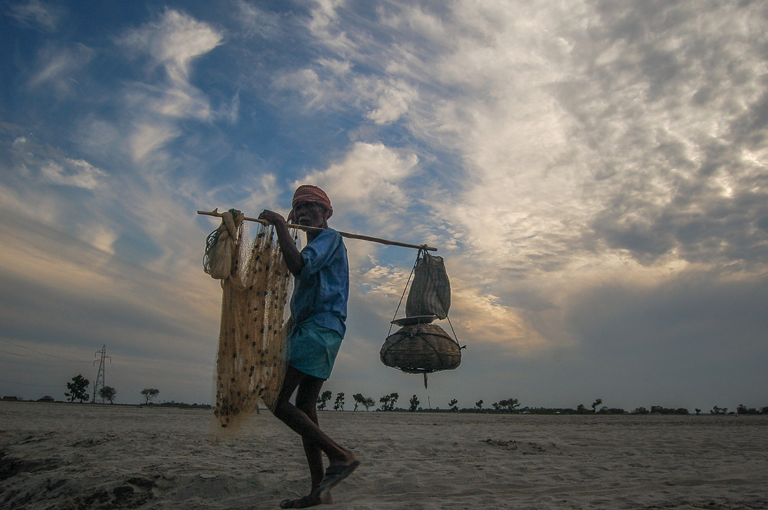 A fisherman returns home with his catch after spending a long day in the Sapta Koshi River in Sundari, where fishing is supplementary to traditional agriculture. Photo: Bijay Gajmer