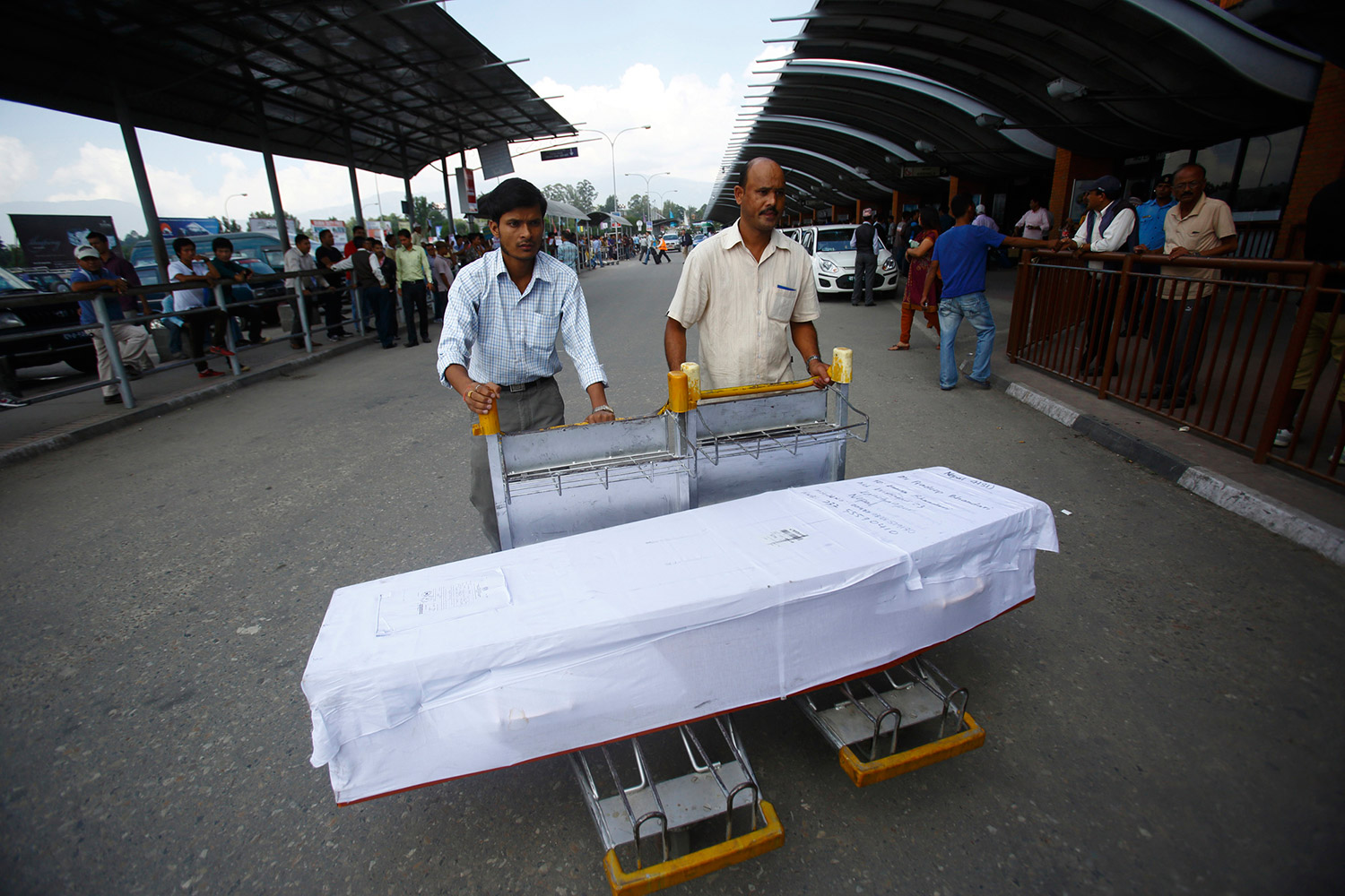 Family members use airport trolleys to transport the dead body of a Nepali migrant worker Pradip Bhandari, who according to his brother was killed in a workplace mishap in Malaysia. As per Department of Foreign Employment, some 3015 Nepali migrant workers died between mid-2006 to April 2014 with the highest number of deaths in Malaysia, Qatar and Saudi Arabia. Fifty-three Nepali workers died in Qatar between January and April 13 this year alone according to The Guardian. October 2013. Photo: Navesh Chitrakar