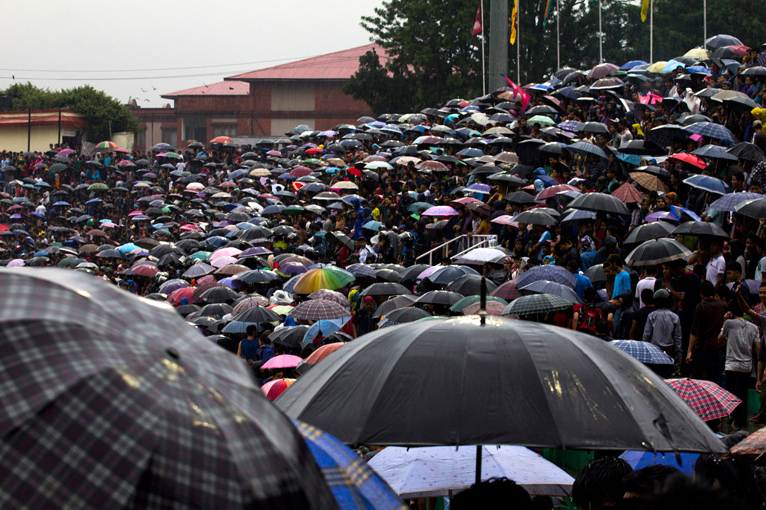 Football fans take shelter from the rain as they watch the final match of the Under 16 SAFF Championship between Nepal and India in Dasarath Rangasala. Photo: Surya Sunuwar