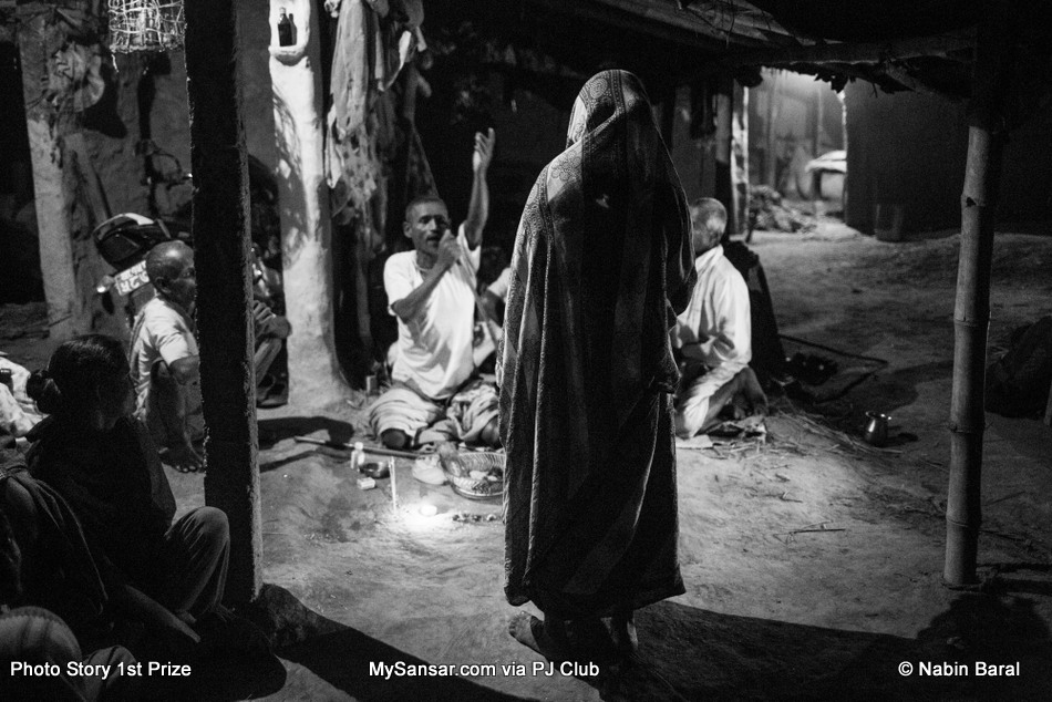 """A women visits a Dhami, the night before attending the """"Ghost Festival"""" to eradicate evil spirits or problems created by family god """"kul deveta""""  supposedly afflicting some of the villagers in Janakpur, a district in Terai region of Nepal. November 4 2014. Janakpur, Nepal."""