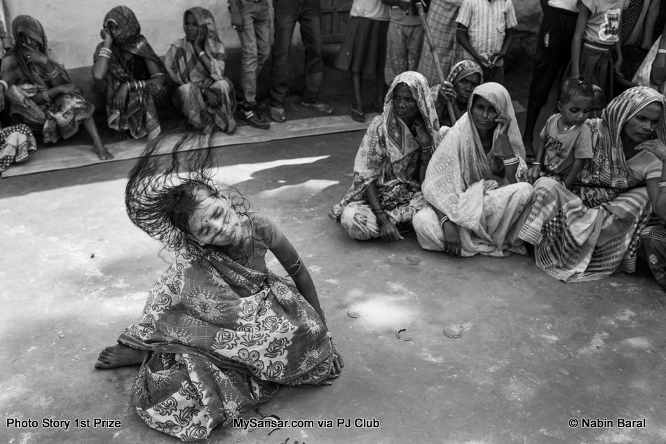 """Another woman believes that she is ill because of a hex placed on her by a evil person or family god """"kul deveta""""  in her village. After visiting a Dhami on the morning of the """"Ghost Festival"""" she is found in a trance state the morning of the banishing ritual festival.  November 5 2014. Janakpur, Nepal."""