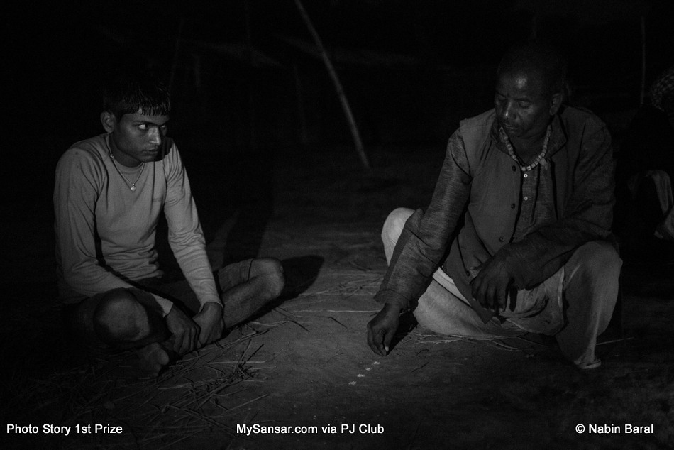 A Dhami,  practices divination to determine the reason of 18 year old Brikeah Yadav 's headaches, body pain and fainting.  The Dhami accuses Kanti Yadev, 103 year old widow villager, of witchcraft practiced on the young man.  November 5 ,2014, Janakpur, Nepal.
