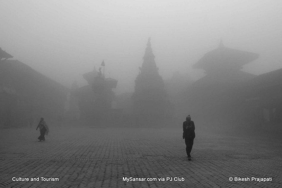 People passingby misty Bhaktapur Durbar Square.
