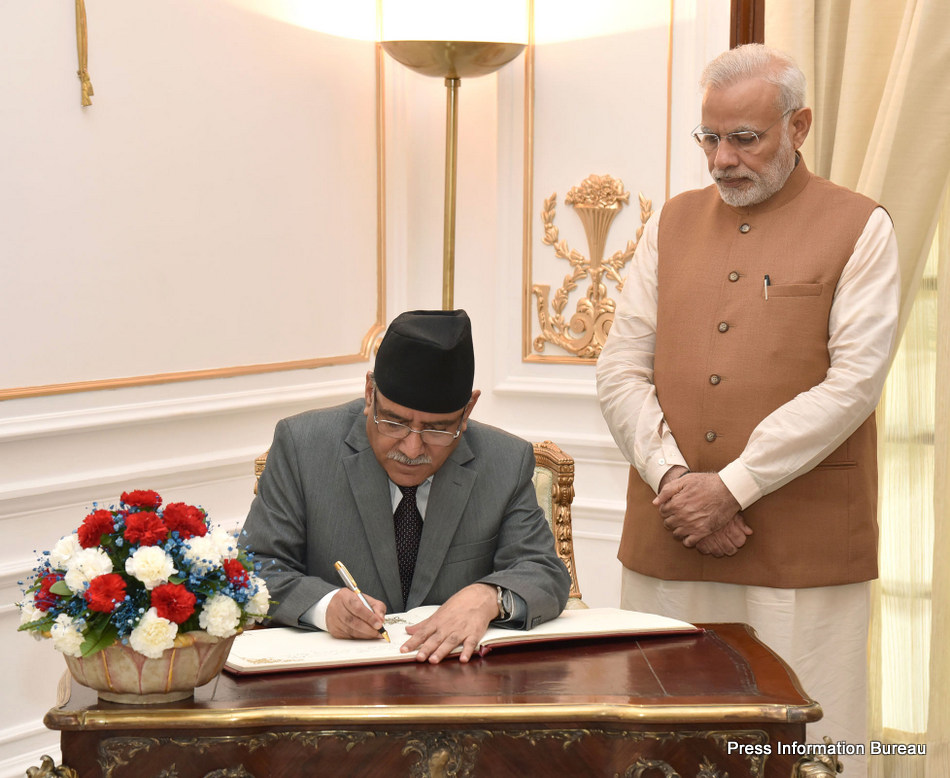 The Prime Minister of Nepal, Mr. Pushpa Kamal Dahal signing the visitor's book, at Hyderabad House, in New Delhi on September 16, 2016. The Prime Minister, Shri Narendra Modi is also seen.